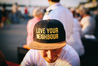 man with cap that says 'love your neighbor'